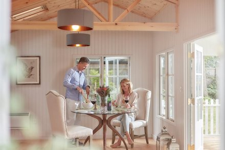 A man and a woman enjoying dinner and a glass of wine inside our Pavilion Garden Room