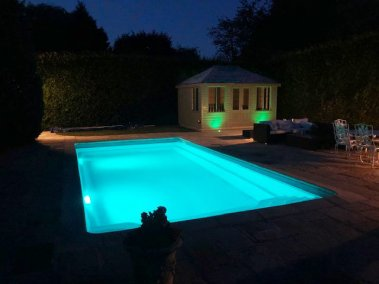 A Cley Summerhouse at night by a swimming pool