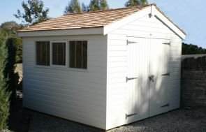 An apex garden shed with cedar shingles covering the roof and double doors providing access in the gable. There are three windows in the side of the building, with one opening and all with stainless-steel security bars. The exterior of the building is clad with smooth shiplap and painted in a light cream colour.
