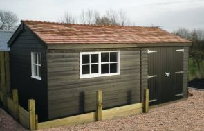An apex garden shed with an attractive cedar shingle roof and Georgian windows. The shed has weatherboard cladding and double door access.