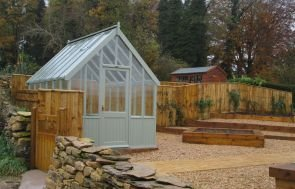 A medium-sized greenhouse pictured in a landscaped vegetable garden with planets and golden gravel. There is a fence and a stone wall around the entire vicinity with gated access via a small wooden gate.