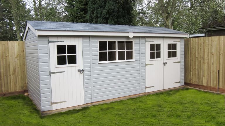 Superior Shed with an apex roof painted in both pebble and ivory. There is smooth shiplap cladding and georgian windows with double doors and a single access door.