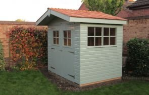 A small apex superior shed with a slight roof overhang and georgian windows. It has double doors with georgian windows and the roof is covered with cedar shingles.