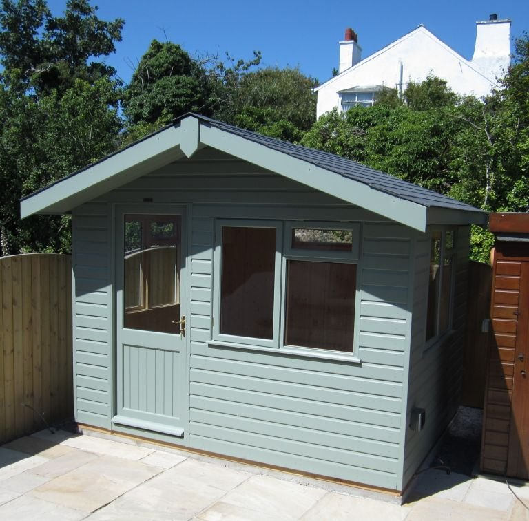 A compact garden studio building with smooth shiplap timber cladding and an apex roof with overhang.