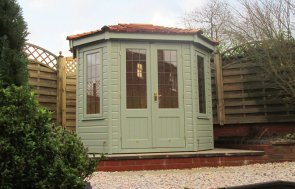 A small Wiveton Summerhouse with shiplap timber cladding and a hipped cedar shingle roof, painted in Sage paint. There are double doors and leaded windows.