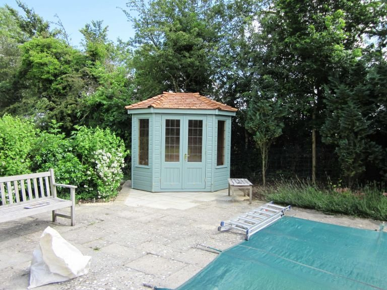 A small Wiveton Summerhouse with shiplap timber cladding and a hipped cedar shingle roof, painted in Lizard paint. There are double doors and leaded windows.