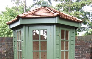 A small Wiveton Summerhouse with shiplap timber cladding and a hipped cedar shingle roof, painted in Lichen paint. There are double doors and windows with Georgian bars.