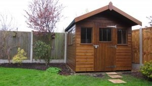 Superior Garden Shed with Overhang and smooth shiplap cladding painted with Walnut preservative stain. The apex roof has a slight overhang on the gable end and a security pack with stainless steel window bars.