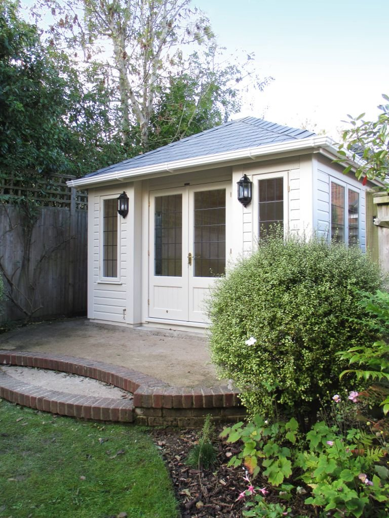 A compact sized garden room atop a raised patio area. The building has a hipped roof covered in grey-slate-composite-tiles and double doors with half-glazed leaded windows.