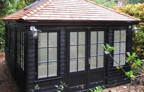 A medium sized garden room clad in weatherboard painted in black exterior paint. The hipped roof is covered with cedar shingles and all windows and doors had georgian bars.