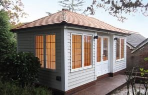 A large garden room with deeper leaded windows and a hipped roof covered in cedar shingles. The exterior is clad with weatherboard timber and painted in the exterior paint shade of sandstone.