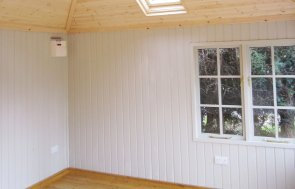 An interior shot showing the inside of a garden room with georgian windows, painted pine lining and electrical pack.