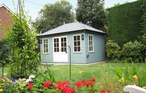 A medium-sized garden room with a hipped roof covered in grey-slate-tiles. The building is positioned in an attractive garden with brightly coloured flowers in the foreground. The building is painted in two-tone contrasting colours of verdigris and ivory and is clad with smooth shiplap.