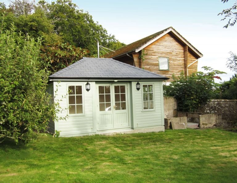 A small garden room with a grey-slate-composite tiled roof and georgian windows. The building has inset doors and corner boards and black guttering along the fascia boards.