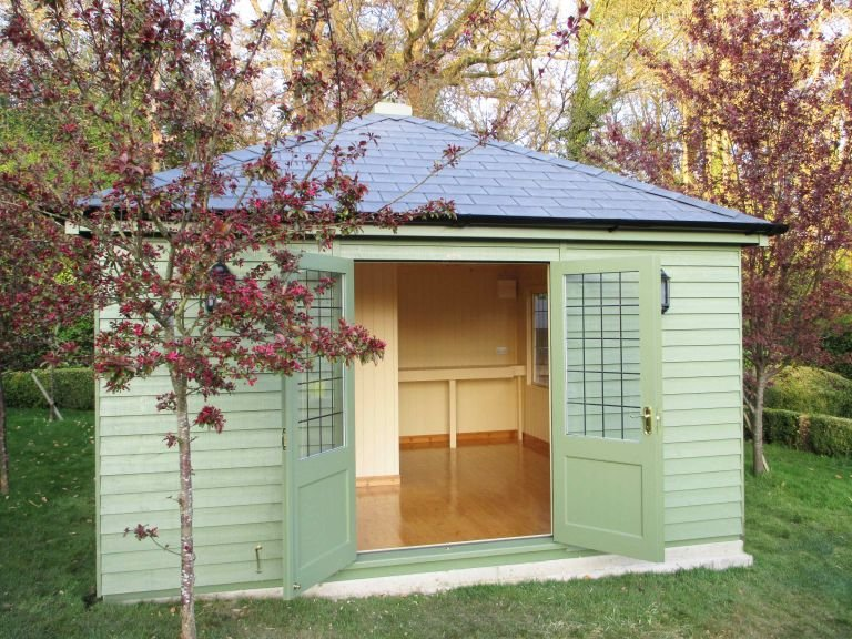 A large garden building with the double doors pinned open to show the interior. The interior has been remodelled and styled as a changing room. The exterior of the building is clad with rustic weatherboard timber and painted in the exterior shade of lichen