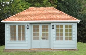 A large sized garden room with a hipped roof covered in cedar shingles with white guttering along the fascia boards. The building is clad with rustic weatherboard and painted in sage exterior paint.