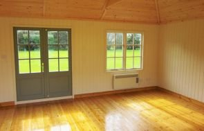 Garden Room Interior image with painted internal lining and georgian windows. The floor is lacquered for durability and there is a heater underneath one of the windows. A ceiling truss is just visible at the top of the image.