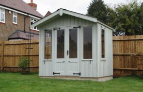 An attractive National Trust summerhouse in a well kept garden beside a timber fence. The building has an apex roof covered with corrugated sheeting with a slight overhang on the gable.