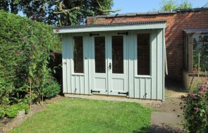 A medium szied national trust summerhouse painted in the shade of disraeli green with rustic cladding sawn vertically.