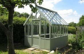 An attractive image of a greenhouse sat beside a vegetable patch atop a concrete base. The exterior is painted in the shade of Lizard.