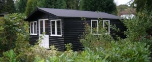 A large garden studio clad with smooth shiplap timber painted in both black and ivory. The apex roof is covered with heavy-duty felt and the building is located in an attractive green area.
