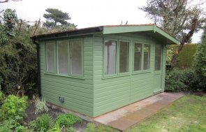 An attractive binham studio is a bespoke size with three window sets and an apex roof with overhang.