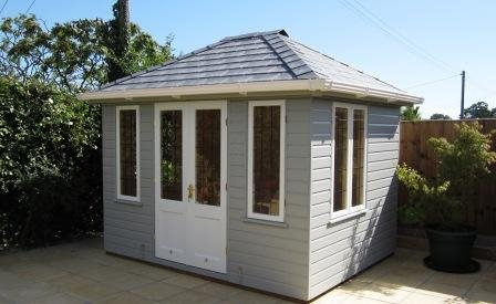 A medium sized summerhouse with a hipped roof covered in slate composite tiles. The windows and doors are painted with ivory whilst the rest of the exterior is painted in pebble grey. There are double doors and two windows on the front of the building, as well as an opening set of windows on the visible left-hand side wall.