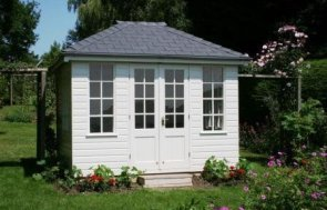 A compact sized summerhouse set among a large garden with lots of flowers and a large grassy lawn.