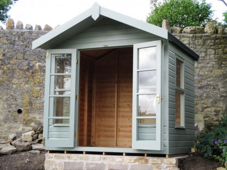 Blakeney Summerhouse with open double doors and a visible interior, the apex roof has a slight overhang and smooth shiplap cladding on the exterior of the building is coated with paint in the sage shade.
