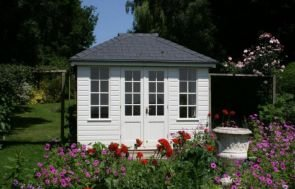Cley Summerhouse with smooth shiplap cladding and a hipped roof covered with slate tiles. It is placed in a very attractive garden with brightly-coloured flowers in the foreground.
