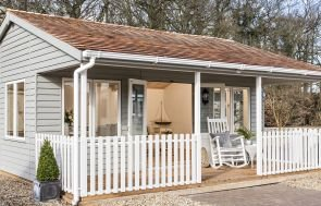 A large pavilion garden room with a veranda beneath the overhang of the apex roof, there is a rocking chair and table on the veranda and double entrance doors that are pinned open to show the interior. The interior features painted matchboard lining and furniture.