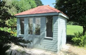 Cley Summerhouse with a hipped roof covered in Red Slate Effect Tiles. The exterior is clad with smooth shiplap and painted in the exterior shade of Lizard. There are double doors on the front of the building that are half-glazed with leaded windows.