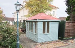 A medium sized summerhouse with a hipped red-tiled roof situated in the back garden of a customer alongside an ornate lamppost and fencing.