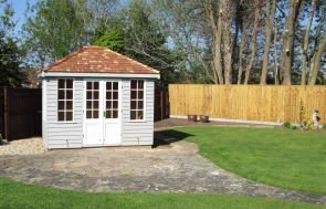 Our attractive cley summerhouse in a large garden with two-tone paint and a hipped roof covered with cedar shingles.