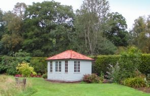 A medium sized cley summerhouse with a hipped roof covered in cedar shingles and georgian windows. The garden is full of shrubbery and colour with trees and a large hedgerow behind.