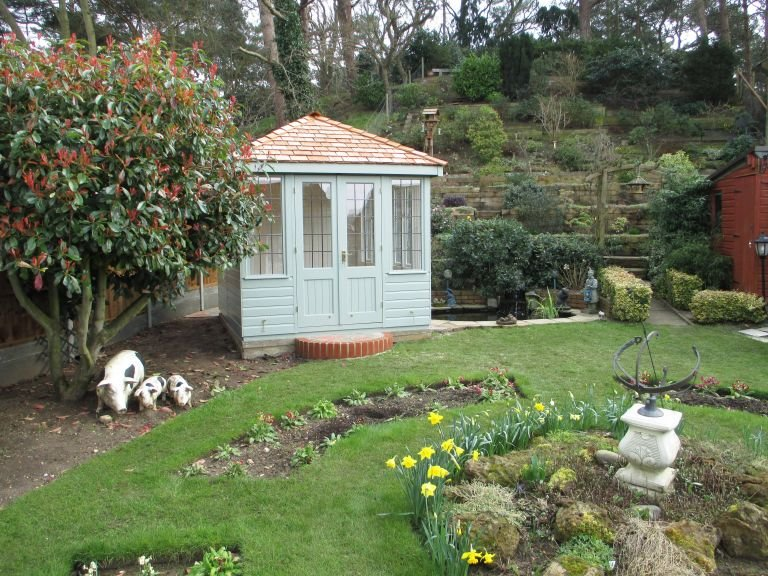 A small cley summerhouse with leaded windows and a hipped roof covered in cedar shingles. Situated in a well-kept garden, the summerhouse is clad with smooth shiplap and painted with the exterior shade of Lizard.