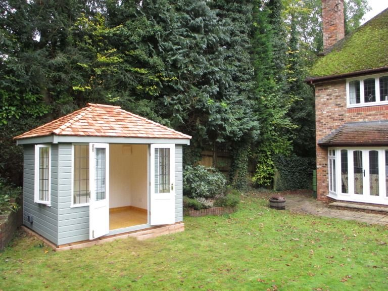 An attractive cley summerhouse with double doors pinned open and the interior visible. The interior features painted lining and electrics.