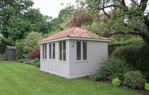 A large cley summerhouse with a hipped roof and shiplap cladding painted in pebble exterior paint