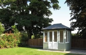 Cley Summerhouse an an attractive spot on a patio beside a wooden fence and tall trees. There is a grassy lawn in front of it that is in the sun. The summerhouse has a hipped roof covered with slate tiles and is painted in the exterior paint shade of Lichen.
