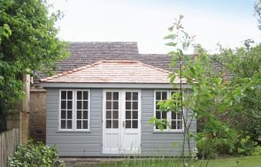 A large cley summerhouse with smooth shiplap cladding painted in grey and a hipped roof covered with red tiles.  The building is painted in a warm grey colour with the windows and doors painted in ivory.