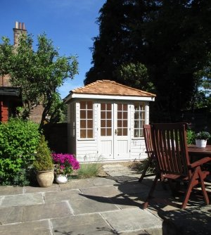 A small, hipped roof summerhouse with georgian bars and smooth shiplap cladding painted in Sandstone exterior paint. The roof is covered with cedar shingles.