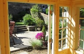 An interior image of a cley summerhouse looking out into the surrounding garden.