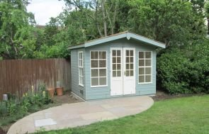 A large summerhouse with an apex roof and slight overhang in a traditional chalet style fashion. Double doors and windows are painted in contrasting colours from the rest of the building.