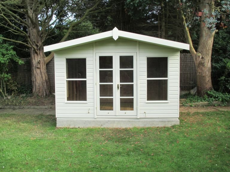 A charming Blakeney Summerhouse positioned on a concrete base atop a green lawn with a backdrop of trees and fencing. The summerhouse itself has an apex roof and double door access with two windows. The smooth exterior shiplap cladding is painted in the light shade of sandstone.