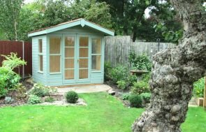 An apex summerhouse with chalet-style exterior and apex roof with overhang.