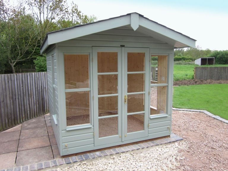 An apex summerhouse with overhang and double doors. Clad with smooth shiplap and internally insulated and lined.