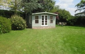 Large blakeney summerhouse with weatherboard cladding and double doors painted in a two tone fashion.