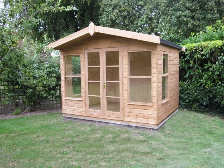 An attractive summerhouse in a tidy garden with trimmed grass and a large hedge behind. The building has an apex roof covered in heavy-duty felt and a smooth shiplap exterior painted in the natural light oak preservative.