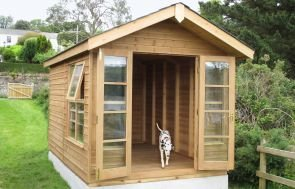 A traditional blakeney summerhouse with windows and doors open. A dog is leaving the building and heading towards the camera. The building has an apex roof and is painted in a natural light oak preservative which allows the natural wood to show through.
