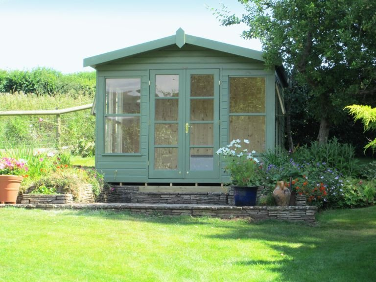 A traditional chalet-style Blakeney summerhouse with an apex roof and interior lining, insulation and electrical pack.